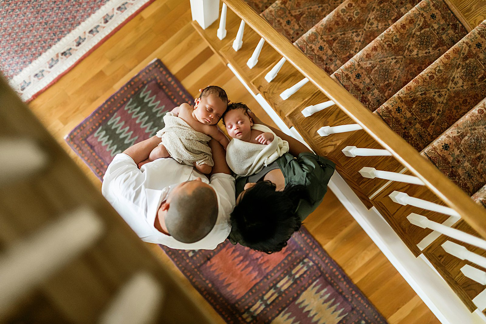 newborn twins photographed from above staircase