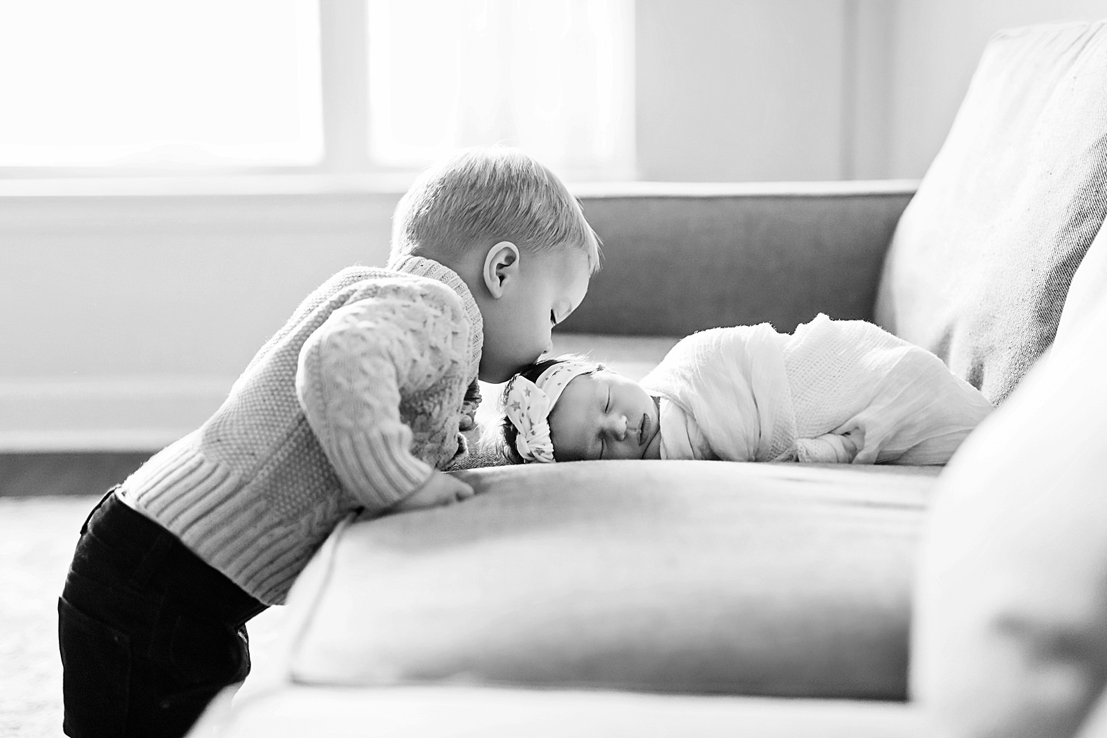brother kisses his newborn sister