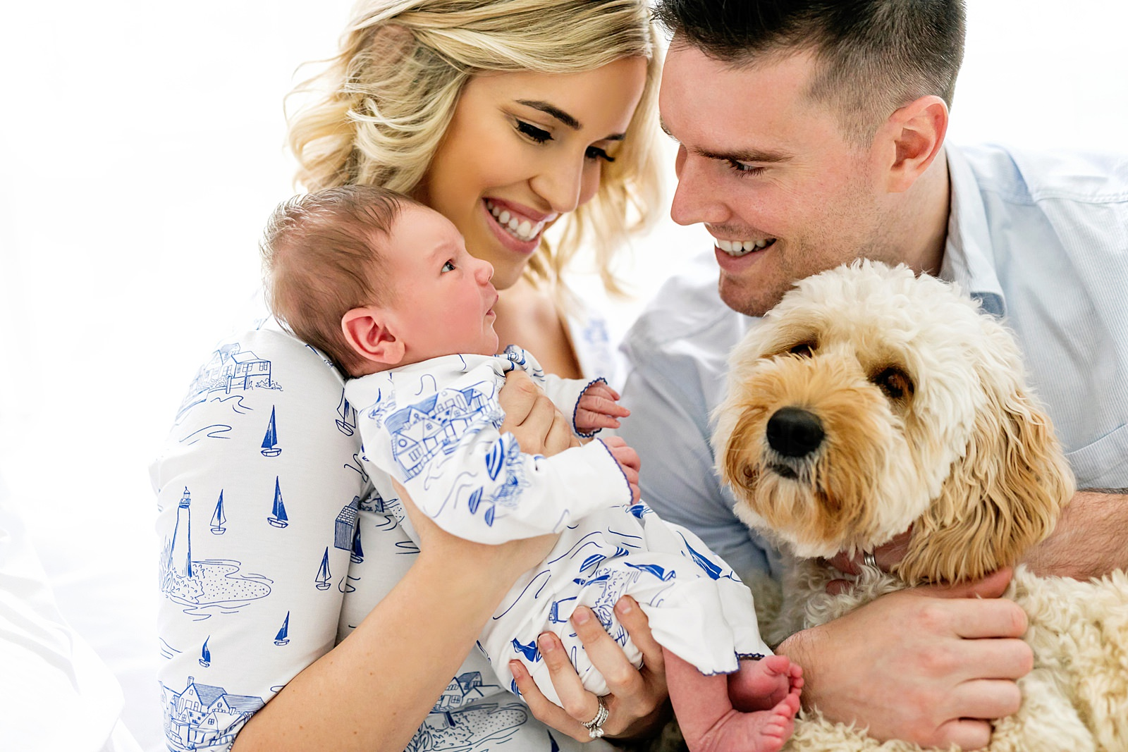 family of four with newborn and dog