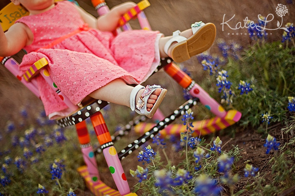 baby girl in painted chair in bluebonnets