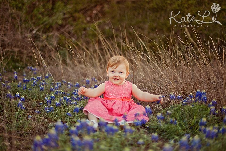 girl wearing pink dress in bluebonnets in San Antonio, TX