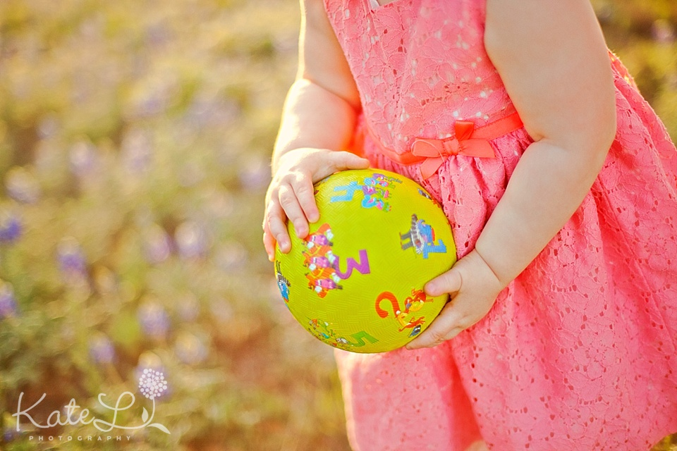 a baby holds a bright green ball in san antonio