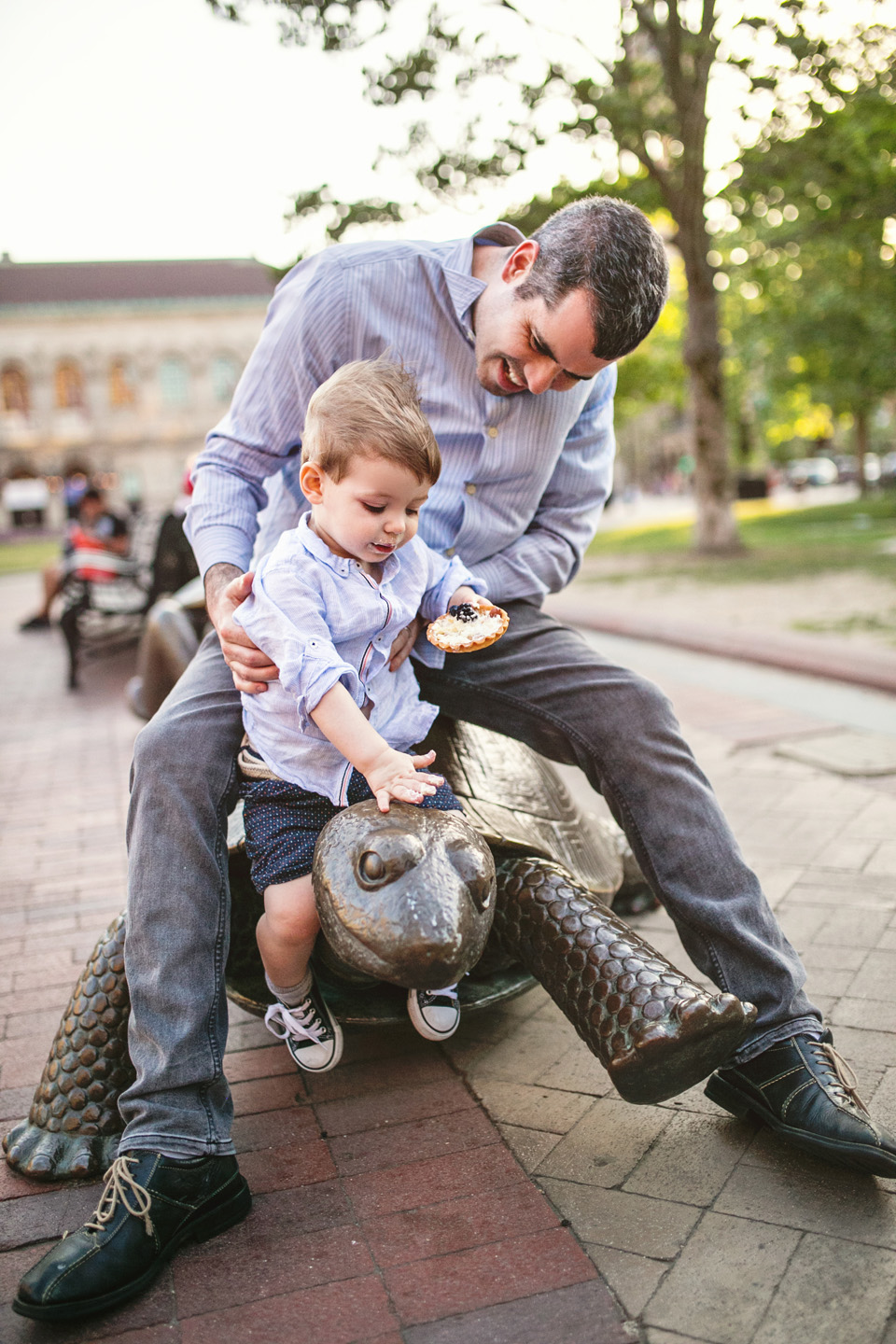 Dad and son play on the turtle in Copley Square.
