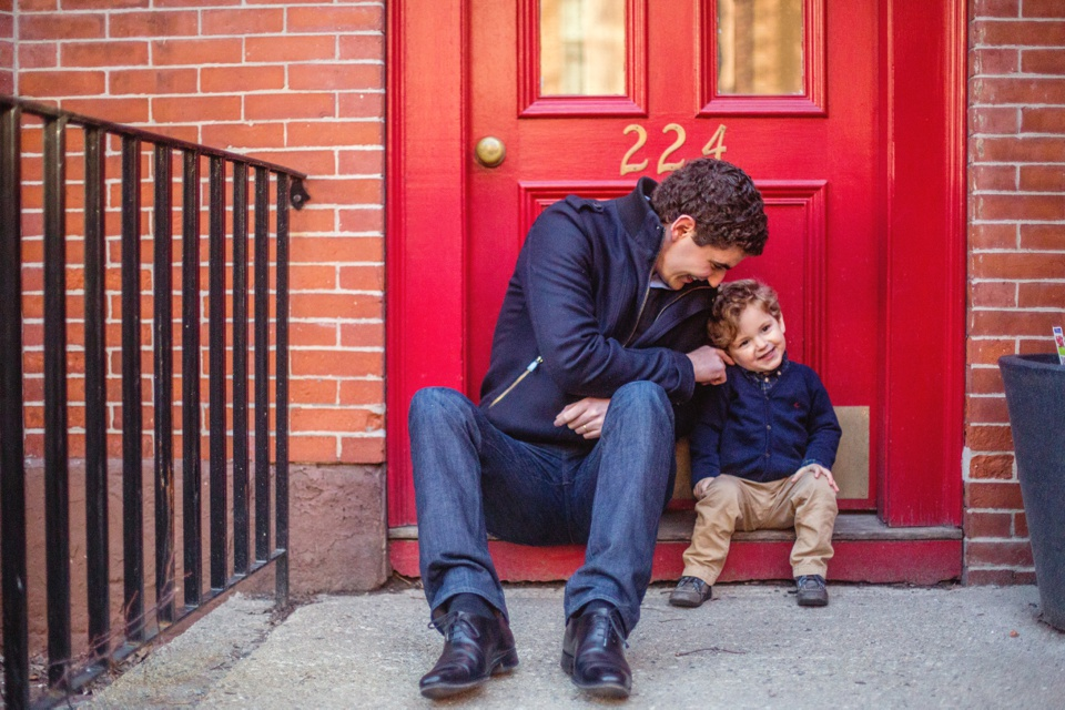 Dad and son play on the doorstep of a red door in Boston's South End.