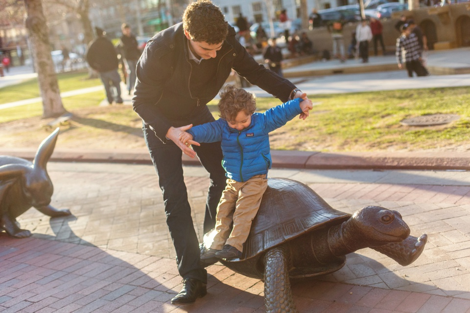 Child plays on the turtle sculpture in Copley Square.