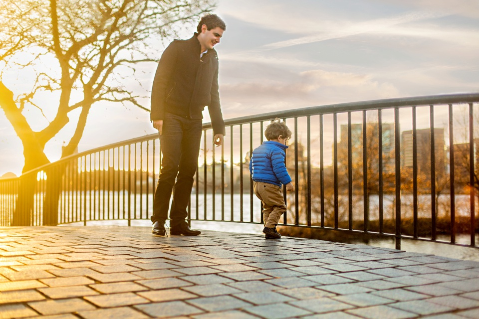 Dad and son play together on the Charles River Esplanade.