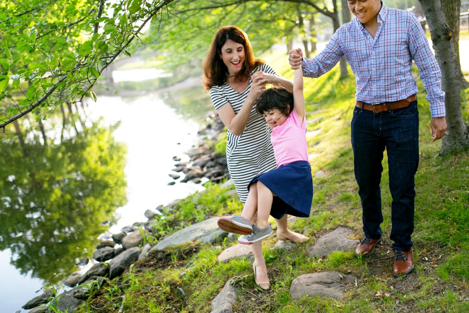 A family is photographed by the charles river in boston.