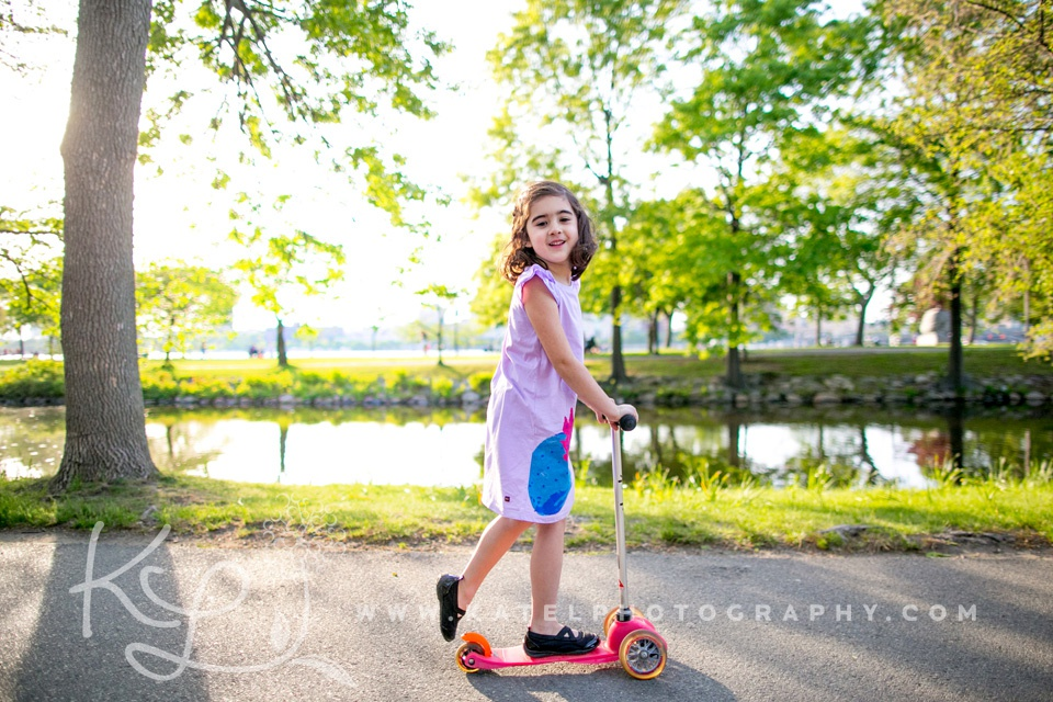 A little girl rides a scooter on the Charles River Esplanade.