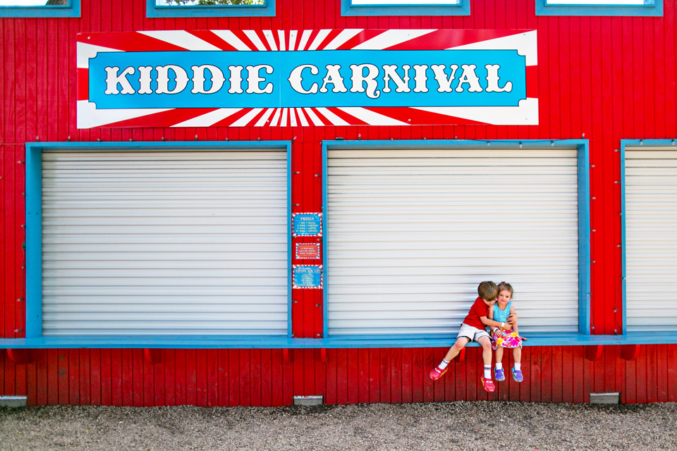 Boston child photographer Kate Lemmon documents two kids playing at a colorful carnival.